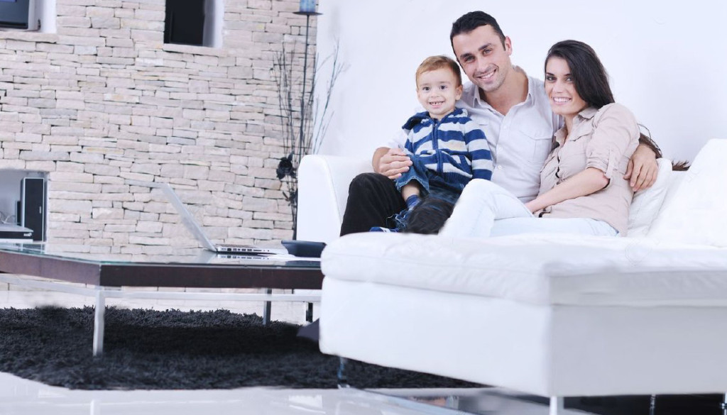 11422709-happy-young-family-have-fun-and-relaxing-at-new-home-with-modern-lcd-tv-in-background-Stock-Photo