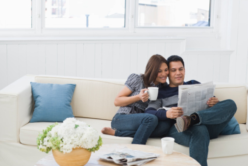Couple reading newspaper on couch at home